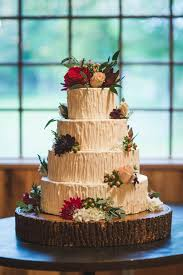 Four Tiered White Wedding Cake On Wood Round Base