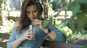 Attractive Woman Relaxing On The Bench In Park And Drinking Iced Coffee Ste