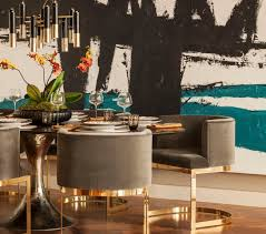 Chic Dining Room Features Large Teal And Black Abstract Art Framing Gold Deco Chandelier Over Table Surrounded By Gray