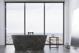 weißes panorama badezimmer mit betonboden weißen wänden massiver grauer badewanne spiegel und tisch mit pflegeprodukten mock der wiedergabe 3d