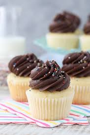 Three Yellow Cupcakes Stacked Together These Are Topped With Chocolate Frosting And Sprinkles