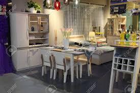 upscale esszimmer in villa in türkis hellblau mit weißen verzierungen dielenboden bücherregal und tisch mit kronleuchter