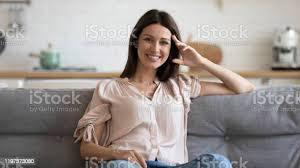 glückliche 30er jahre frau sitzt auf gemütlichem sofa im wohnzimmer stockfoto und mehr bilder abgeschiedenheit