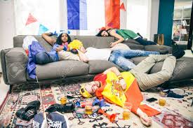 gruppe freunden schlafen in einem wohnzimmer nach der betrunkene unterstützer ruhen nach dem feiern ihrer teams bei einem sport event