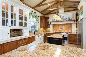 Country Style Kitchen With Rustic White Cabinet Uppers And Brown Lower Cabinets Beige Granite Island