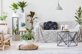 hocker neben tisch und sofa mit dunklen kissen kissen im natürlichen wohnzimmer interieur mit pflanzen