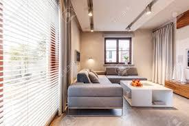 graue ecke und weißes tisch im beige wohnzimmer mit lichtern und fenster