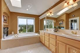 luxus badezimmer interieur orange braunen wänden und gewölbedecke mit oberlicht große spiegel und zwei waschbecken bad eitelkeit northwest usa