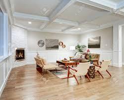 lovely handwerker stil wohnzimmer mit kassettendecke über hellbeige wände mit brett und latten holzvertäfelung stein eckkamin und gemütliche sofas
