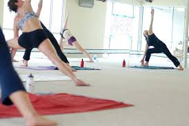 Students Hold A Pose During Bikram Yoga Class In The Sauna Like Studio On