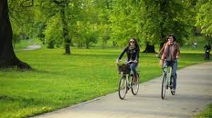 Carefree Female Friends Are Riding Together And Smiling Two Pretty Women With Bicycles Having