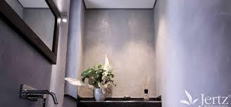 ein badezimmer ohne fliesen mit marmorputz und zementboden