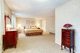 helles schlafzimmer mit weichem teppichboden beige tapeten zimmer mit antiken doppelbett großer schrank mit spiegel nachttische eingerichtet