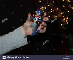 Hand Holds Christmas Tree Ornament Of Dophin With Camera In Front Bokeh