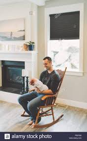 Father Sitting In Rocking Chair Holding Newborn Baby Boy ... Boston Nursery Rocking Chair Baby Throne Newborn To Toddler 11 Best Gliders And Chairs In 2019 Us 10838 Free Shipping Crib Cradle Bounce Swing Infant Bedin Bouncjumpers Swings From Mother Kids Peppa Pig Collapsible Saucer Pink Cozy Baby Room Interior With Crib Rocking Chair Relax Tinsley Rocker Choose Your Color Amazoncom Wytong Seat Xiaomi Adjustable Mulfunctional Springboard Zover Battery Operated Comfortable
