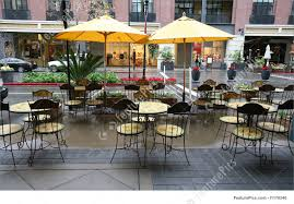 Outdoor Cafe Chairs And Tables Of A Restaurant Seating Outside With Shopping Center Background