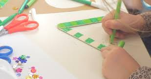 Kids Girls Hands Are Coloring A Triangle With Green Marker Sequins And Scissors On Table Close Up Sitting At The
