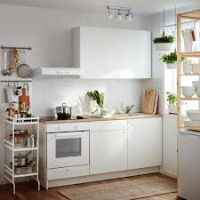 A Small White Kitchen Consisting Of Complete Base Cabinet With Doors Drawers Worktop