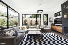 schwarzweißschema wohnzimmer mit holz und grauen fliesen akzente und chevronmuster boden teppich stockfoto und mehr bilder architektur