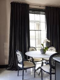 White And Black Dining Room Features A Round Marble Top Table Surrounded By Back Chairs Upholstered In Skull Fabric