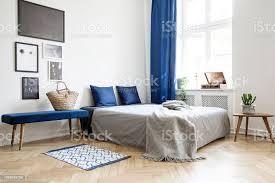 schlafzimmer design in modernen wohnung bett mit dunkel blauen kissen und graue bettdecke und decke neben fenster echtes fotokonzept stockfoto und