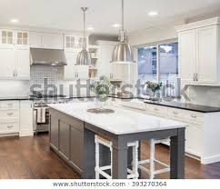 Beautiful Kitchen In Luxury Home With Island Pendant Lights Cabinets And Hardwood Floors