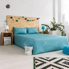 blaue bettdecke auf dem bett im modernen unbedeutenden schlafzimmer mit diy hippie möbeln