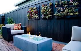 wohnzimmer auf holzterrasse mit holzgartenmauer und