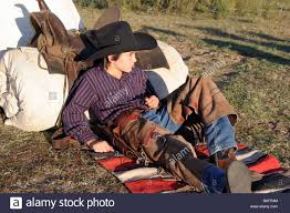 Cowboy Bed Roll by A Young Cowboy Resting Against His Bed Roll And Saddle Out On The
