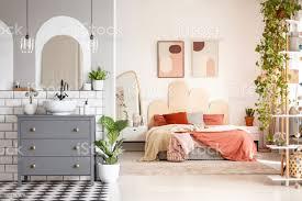 echtes foto einem badezimmer mit einem schrank waschbecken und ein spiegel neben einem schlafzimmer innenraum mit einem breiten bett zwischen