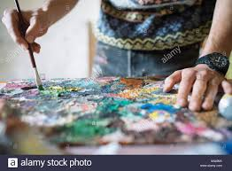 Male Artist Mixing Oil Paint On Palette In Artists Studio Close Up Of Hands