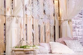 schlafzimmer loft design mit weichen kissen betthimmel swing mit weißen tulpen traumfänger mit federn und perlen hängen an einem hölzernen hintergrund