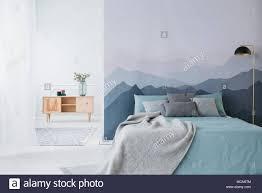 blau bett mit grauen decke gegen berg tapete in einfache