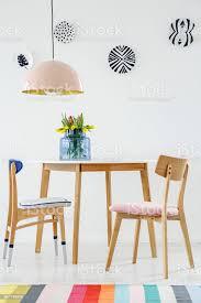 bunte esszimmer interieur mit tisch stühlen gestreiften teppich pastell kronleuchter und hängenden platten an der wand stockfoto und mehr bilder