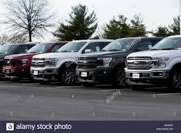 A Row Of New Ford F-series Pick-up Trucks At A Car Dealership In ...