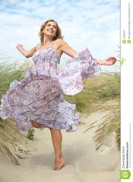 woman with dancing with summer dress at the beach royalty free
