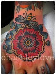 Simple Designed Multicolored Mexican Traditional Tattoo With Flower And Big Bee On Hand