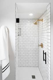 white subway shower tiles with gray grout and brushed gold shower