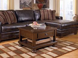 Living Room Dark Brown Leather Sofa With Stripped Rug Combined Square Wooden Table