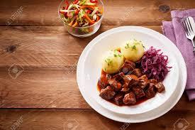 traditionelle deutsche küche mit leckerem rindsgulasch und gekochten knödeln serviert mit zerkleinertem purpurkohl und einem frischen salat