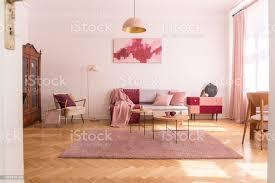 trendige wohnzimmer interieur mit grau mit pastell rosa kissen und decke stilvolle beige sessel mit burgunder kissen und retroschrank in der