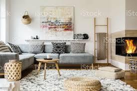 holztisch neben grauen ecke sofa im warmen wohnzimmer interieur mit malerei und kamin echtes foto stockfoto und mehr bilder boho stil