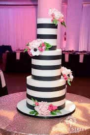 Hot pink and blush pink flowers pop against a background of modern black and white fondant