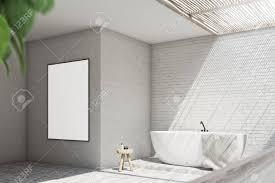 graues badezimmer interieur mit einer weißen badewanne einem kleinen stuhl mit cremes einem handtuch und einem großen vertikalen poster an der wand