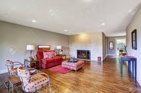 geräumige moderne wohnzimmer mit hellen roten möbeln und roten teppich auf parkett ansicht gebäu kamin in der mauer