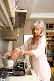 femmes plus cuisine eau bouillante de femme plus âgée sur le dessus de fourneau de