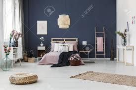 malerei hängen auf dunkelblauen wand im gemütlichen schlafzimmer mit frischen blumen