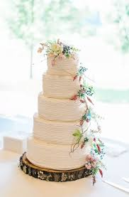 The Five Tier White Wedding Cake Was Decorated With A Cascade Of Greenery And Wildflowers