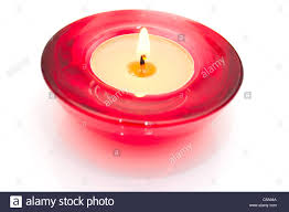 Burning Candle in Red Glass Candlestick on White Background