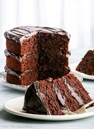 A delicious piece of the healthy paleo chocolate cake on a white plate with a sliver